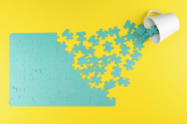 Puzzle and cup on a yellow background