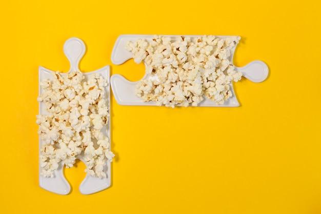 黄色の背景にポップコーンとパズル料理。映画を見るのに最適な会社