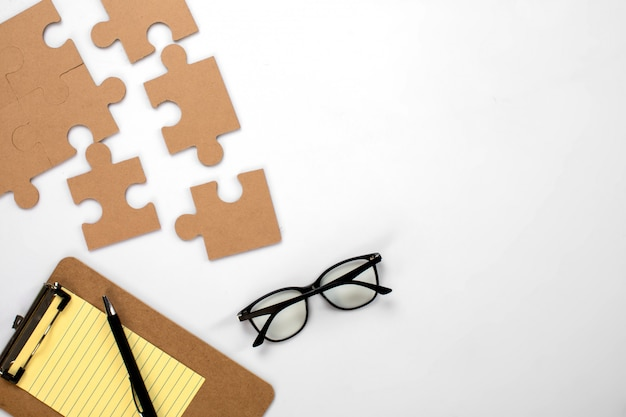 Puzzle glasses and yellow notepad
