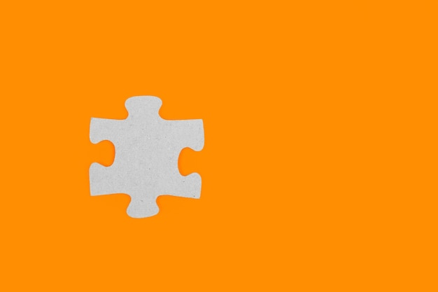 A puzzle piece on a orange background in a close up view