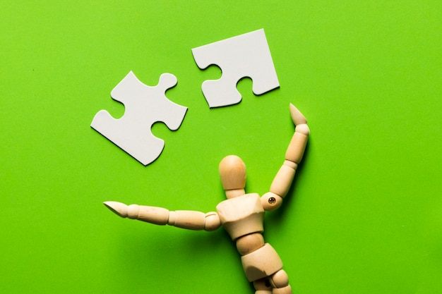 Puzzle piece with wooden human figure on green backdrop