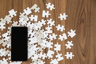 パズルのピースとスマートフォンの木製のテーブル