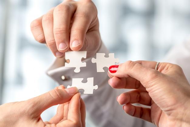 パズルのピースが3つの男性と女性の手で一緒に取り付けられている
