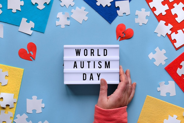 Puzzle pieces, text world autism day on lightbox. blue flat lay, top view with jigsaw puzzle pieces