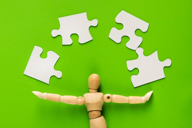 Puzzle pieces with wooden human figure over green background
