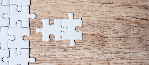 Puzzle pieces on wood table background. business solutions, mission target, successful, goals, cooperation, partnership and strategy