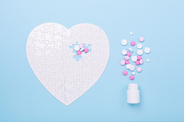 Puzzle in shape of heart white and pink pills on blue