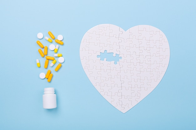 Puzzle in shape of heart white and yellow pills on blue