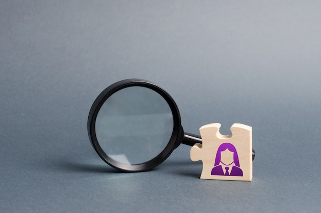 Puzzle with business woman symbol and magnifying glass. search for a new employee