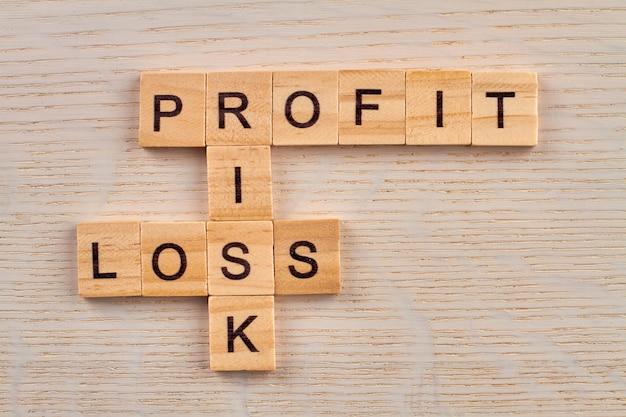 경제적 용어로 퍼즐. 투자는 항상 위험합니다. 나무 보드에 나무 블록으로 만든 손익.
