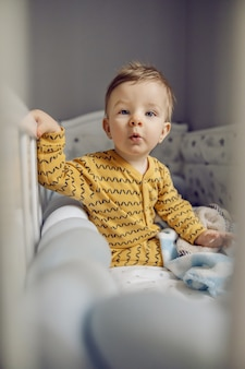 Puzzled adorable blond little baby boy sitting in his crib in the morning and preparing to stand up.