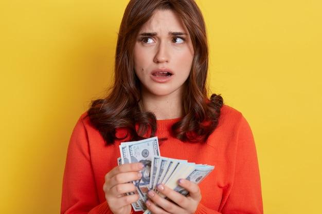 オレンジ色のセーターを着て、口を開けて黄色い壁の上に孤立して立って目をそらし、現金を手に持って過ごし方を考える、困惑した愛らしいヨーロッパの女性。