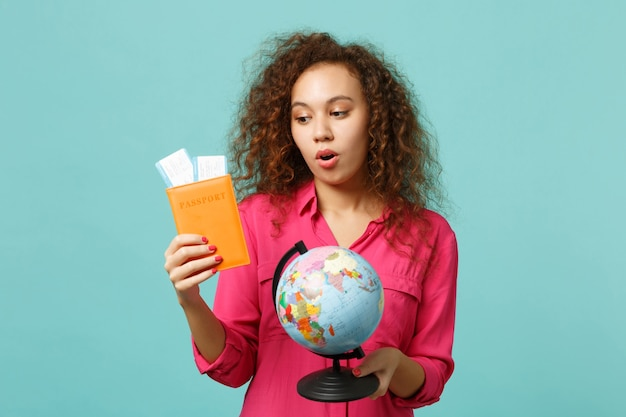 Puzzled african girl in casual clothes holding earth world globe, passport boarding pass ticket, isolated on blue turquoise background. people sincere emotions, lifestyle concept. mock up copy space.