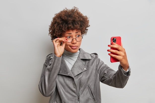 Puzzled afro american woman keeps smartphone in front has video call talks with colleague or partner discuss future plans wears round transparent glasses and grey jacket