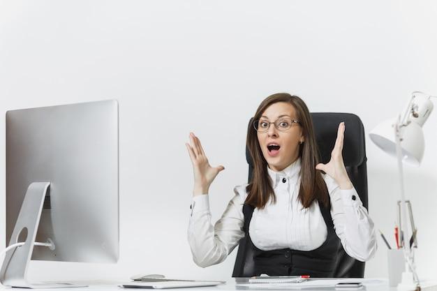 양복과 안경을 쓴 갈색 머리 비즈니스 여성이 책상에 앉아 밝은 사무실에 문서가 있는 현대적인 모니터로 컴퓨터 작업을 하고 손을 펼치고 있습니다.