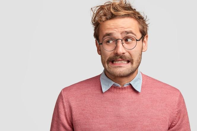 困惑した魅力的なあごひげを生やした感情的な男が眼鏡をかけ、心配そうな恥ずかしい表情を脇に置いて見える