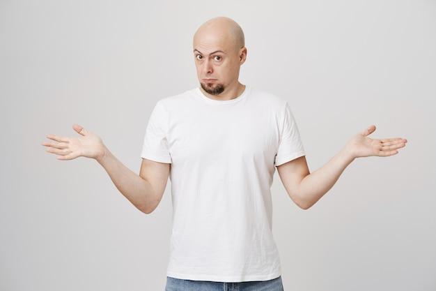 Puzzled bald guy spread hands sideways, can't understand