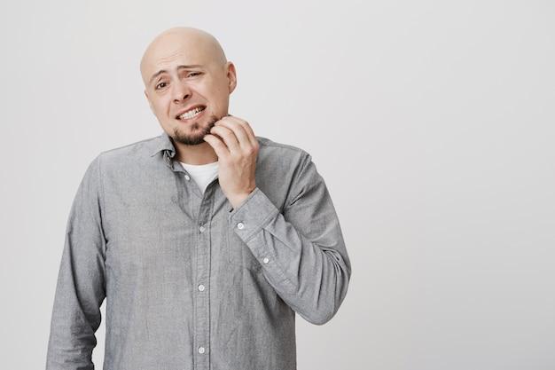 Озадаченный лысый мужчина почесывает бороду, чешется