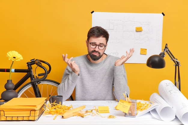 Puzzled bearded adult man looks doubtful at architectural sketch shrugs shoulders as doesnt know how to improve it spends much time on work sits at desktop with blueprints for future project
