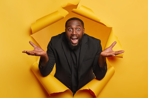 Puzzled bearded afro man spreads palms  feels hesitant and unaware, acts clueless what happened, wears formal black suit, poses in ripped yellow paper hole indoor