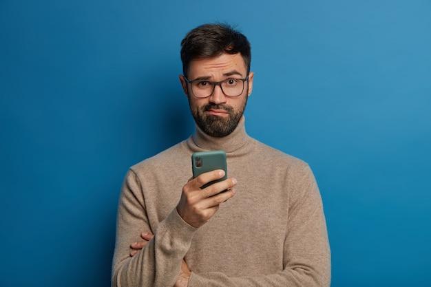 Озадаченный бородатый парень в очках пользуется современным мобильным телефоном
