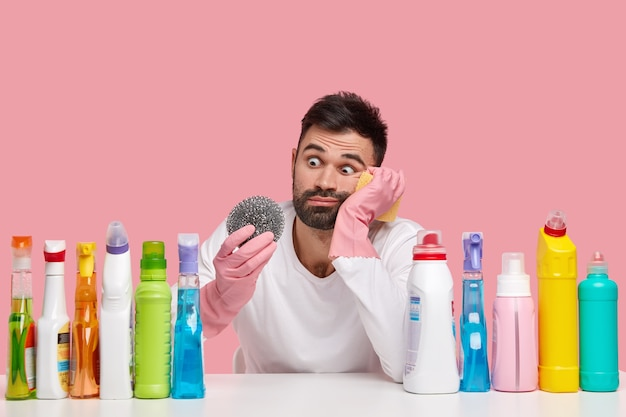 Puzzled bearded man looks with stupefied expression at sponge, wears protective gloves, sits at desk with cleaning agents