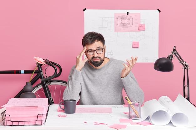 Озадаченный бородатый мужчина поднимает руку держит руку на храме, сталкивается с трудной задачей, не может найти решения, носит повседневную одежду, позирует в коворкинге у розовой стены. нерешительный мужчина-архитектор.