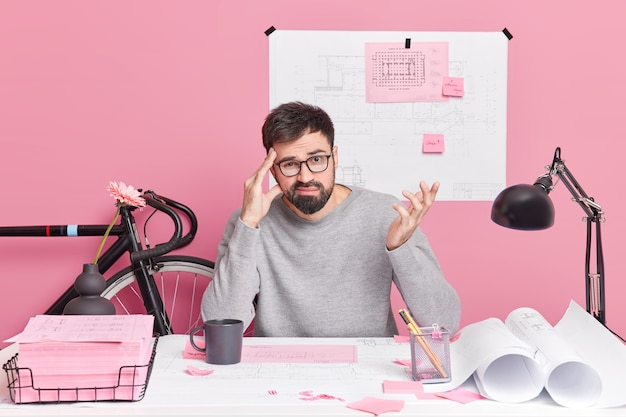 Puzzled bearded man raises hand keeps hand on temple faces difficult task cannot find solution wears casual clothes poses in coworking space against pink wall. hesitant male architect.