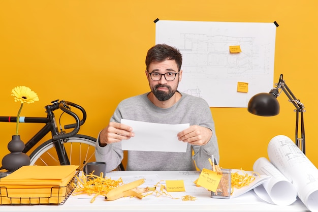 Puzzled bearded skilled male illustrator holds paper has troubles with future project poses in coworking space has mess on desk. man freelance architect prepares new house development drawings