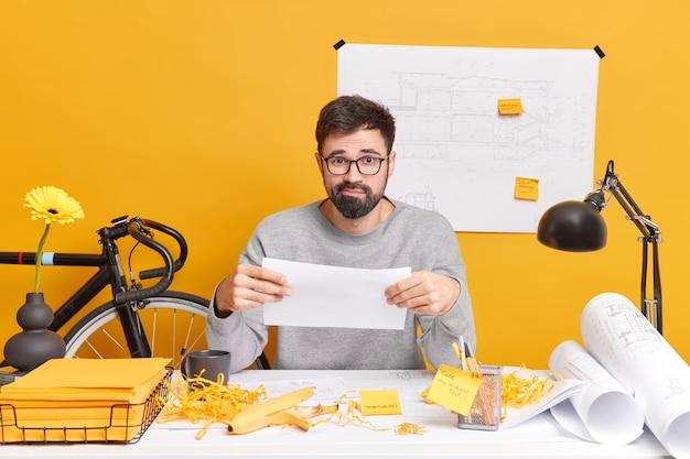 困惑したひげを生やした熟練した男性イラストレーターは、紙を保持し、コワーキングスペースでの将来のプロジェクトのポーズに問題があり、机の上に混乱があります。男性フリーランス建築家が新しい住宅開発図面を作成