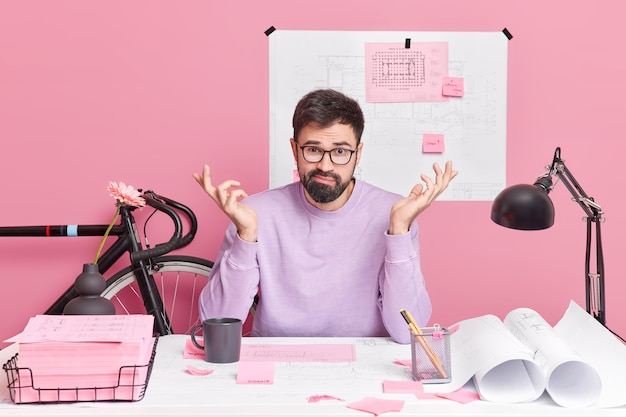Puzzled bearded skilled man shrugs shoulders poses in coworking space creats architect project using blueprint sketches surrounded with memo stickers faces some problems during working process