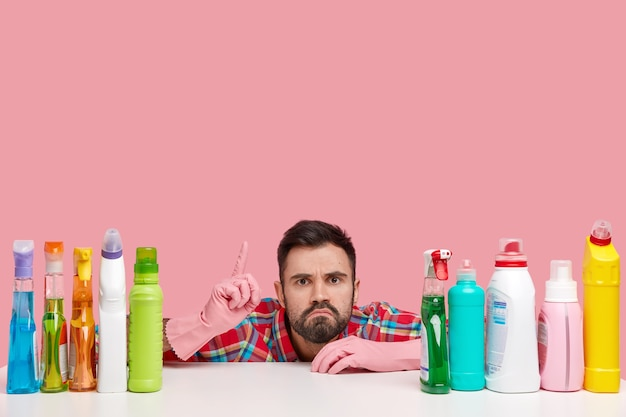 Puzzled bearded young man points upwards, has displeased expression, shows place to clean, uses high quality detergents