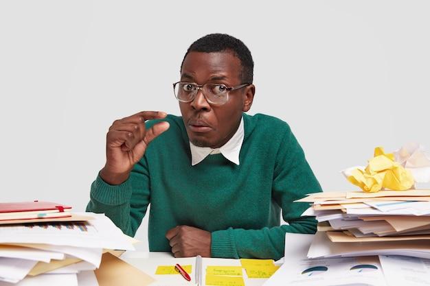 Ragazzo afroamericano nero perplesso con i capelli corti, fa piccoli gesti, ha un'espressione facciale confusa, dimostra quanto tempo ha per finire il lavoro