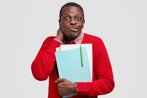 Озадаченный черный этнический школьник недоуменно поджимает губы, прижимает к себе бумаги и учебники, носит красную одежду.