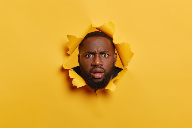 Puzzled black man with thiсk bristle, looks with angry surprised face expression, keeps head in torn paper hole, stands bothered and disappointed. yellow background