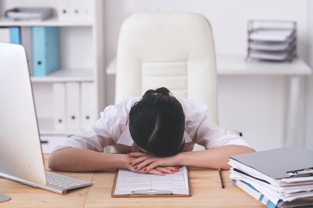 요청을 처리하는 동안 신청서와 함께 테이블에 누워 직장에서 피곤한 의아해 갈색 머리 여자