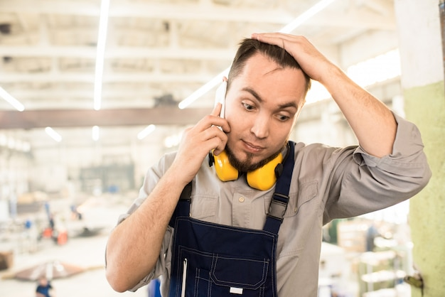Puzzled builder calling on phone from construction site