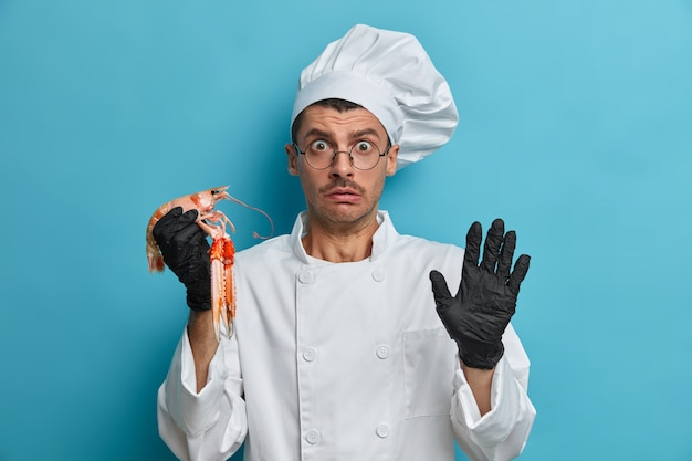 何かを恐れて、アカザエビ料理を調理しようとしている困惑したシェフ