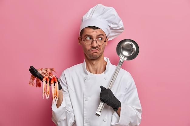 Lo chef perplesso tiene gamberi crudi e mestolo, prepara la zuppa di frutti di mare, indossa l'uniforme, il cappello, gli occhiali rotondi, prepara la cena al ristorante