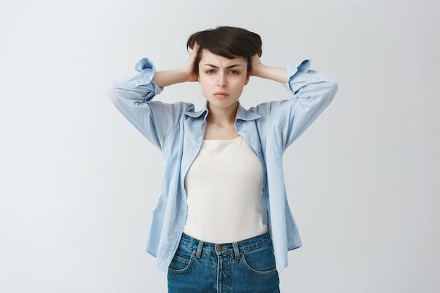 Озадаченная, сложная милая девушка, держащая руки за голову, с большой проблемой, слишком много размышлений