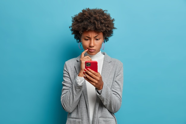 Puzzled confused dark skinned woman in formal wear looks indignant at smartphone, gazes at display, reads business news on website,