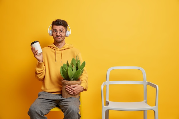 Puzzled confused european man listens favorite music in headphones drinks coffee to go and sits alone near empty chair holds potted cactus