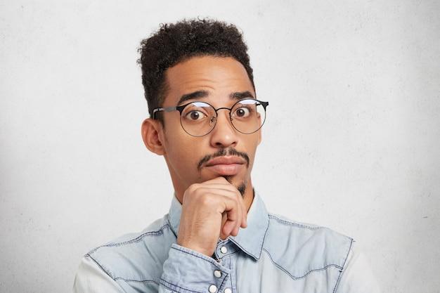 Perplesso confuso bell'uomo dalla pelle scura con acconciatura afro tiene la mano sul mento, guarda con stupore
