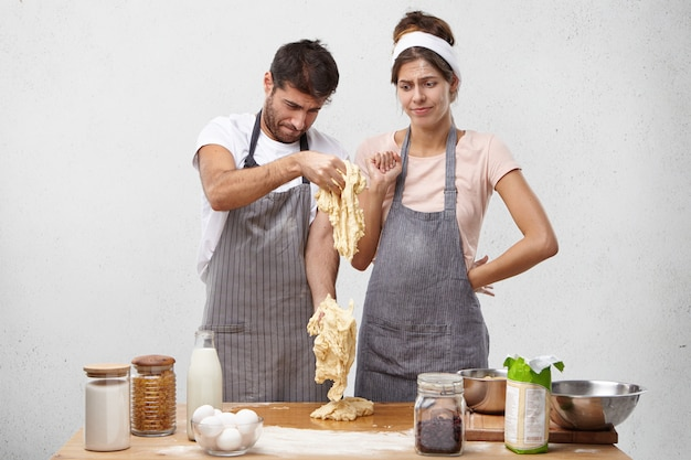 Puzzled couple look at bad made dough, have unsuccessful day, did by wrong recipe