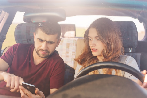 Puzzled couple sits in automobile, bearded man holds smart phone, uses online maps, tries to find way, being lost, have journey on weekend. family in automobile chek email while parking on road side.