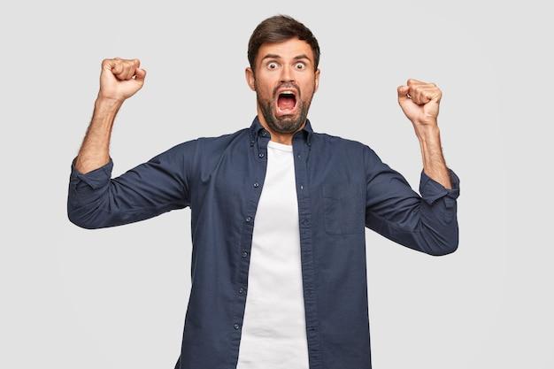 Maschio pazzo perplesso con espressione spaventata, urla forte e disperatamente, tiene le mani serrate a pugno, ha un aspetto fantastico, vestito casual, isolato su un muro bianco. persone e concetto di reazione