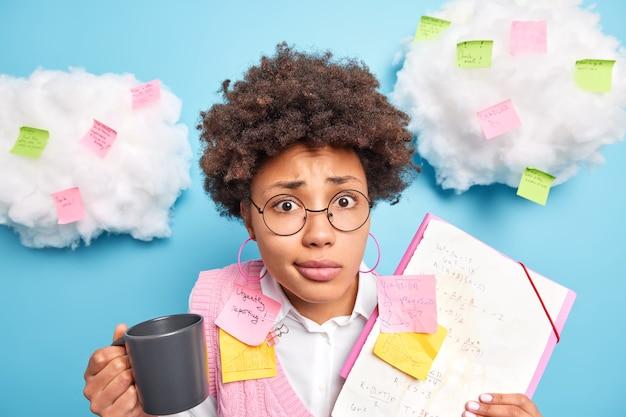 Perplesso riccio studente afroamericano della facoltà di matematica ha pausa caffè tiene tazza con documenti per bevande con adesivi memo rende i piani di progetto la strategia si prepara per gli esami indossa bicchieri trasparenti
