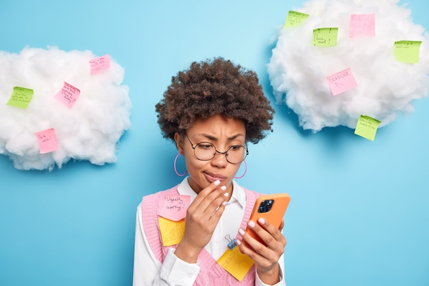 Puzzled curly haired busy female office work has many plans for weekday concentrated at smartphone reads message surrounded with colorful sticky notes not to forget about urgent things to do