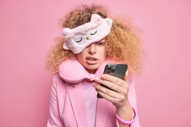 困惑した巻き毛の女性がスマホディスプレイで不機嫌な表情に集中して目覚めた後、メッセージの内容をチェック重要な会議を忘れてスリープマスクとネックピロースタンドを屋内に