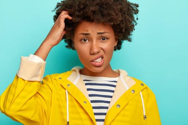 困惑した巻き毛の女性は頭を掻き、顔を笑い、カメラを混乱させて見、厄介な状況に直面し、黄色の防水レインコートを着て、青い背景の上に隔離